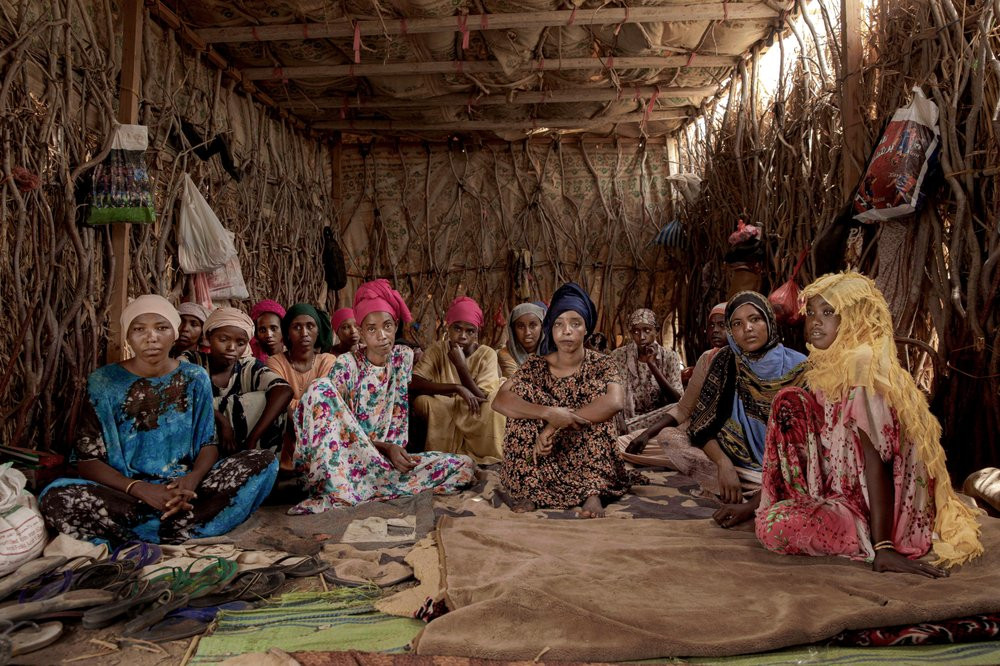 """In this July 25, 2019 photo, Ethiopian migrant girls sit inside in a lockup known in Arabic as a """"hosh,"""" in Ras al-Ara, Lahj, Yemen. Some lockups hold as many as 50 women at a time. The women will stay here for several days until their transportation is ready. (AP Photo/Nariman El-Mofty)"""