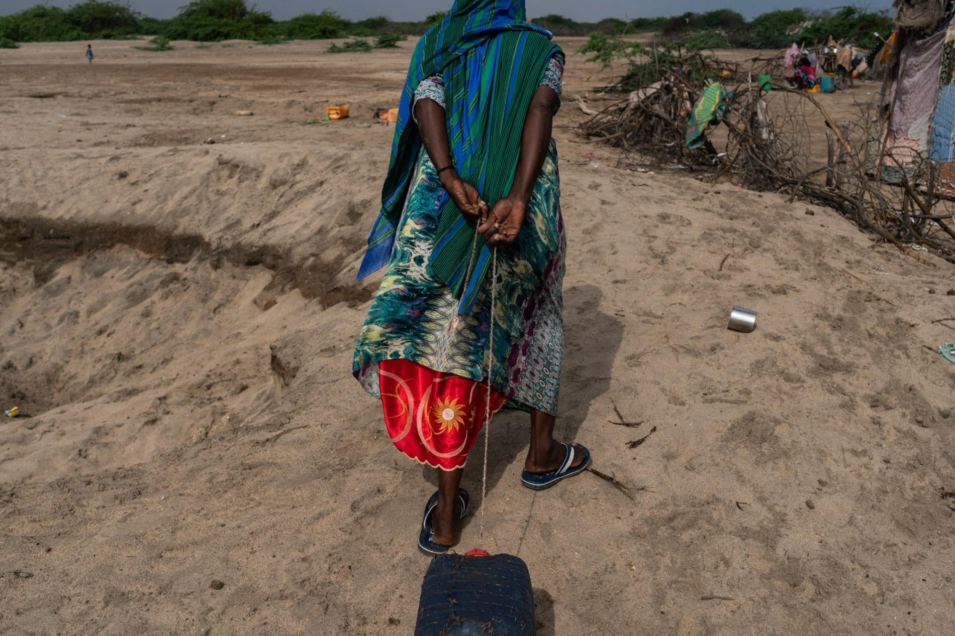 Guude Aadan drags water from a hole dug in the ground in Hijiinle. She came here from her home village of Topta, after drought in 2017 killed her herd of 70 goats and sheep. She now depends on humanitarian aid—and food gifts from relatives.