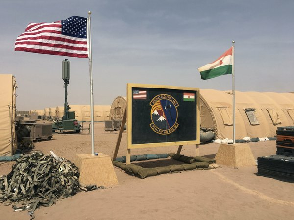 FILE- In this file photo taken Monday, April 16, 2018, a U.S. and Niger flag are raised side by side at the base camp for air forces and other personnel supporting the construction of Niger Air Base 201 in Agadez, Niger. As extremist violence grows across Africa, the United States is considering reducing its military presence on the continent, a move that worries its international partners who are working to strengthen the fight in the tumultuous Sahel region. (AP Photo/Carley Petesch, File)