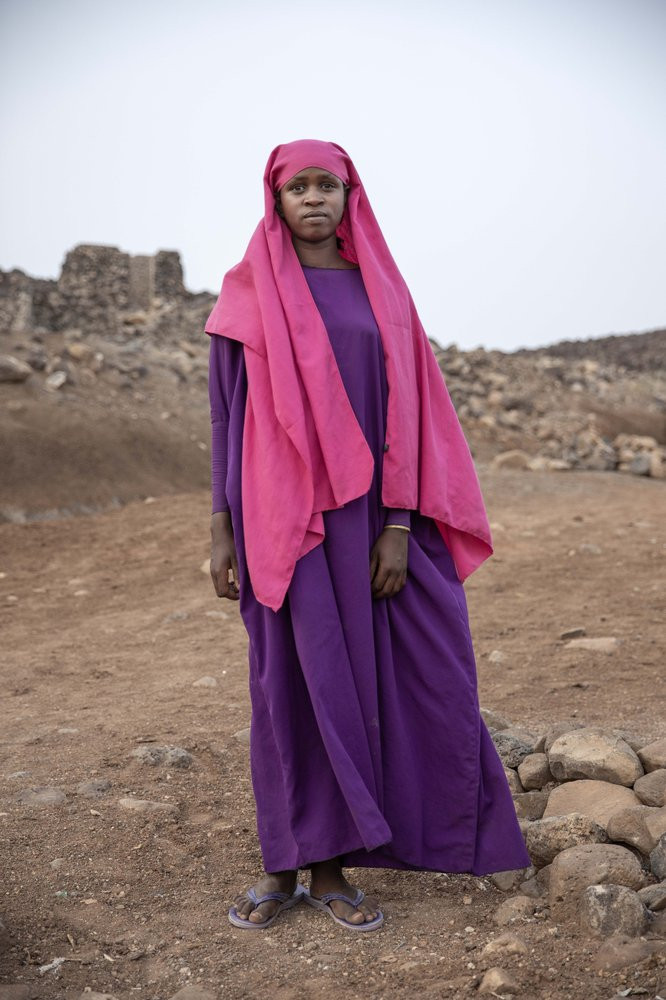 In this July 12, 2019 photo, 17-year-old Ikram Abdi, a migrant from Ethiopia, poses for a portrait in a slum area of Dikhil, Djibouti. Like many of the migrants, she left at dawn without her families' knowledge and hoped for their forgiveness when she starts sending them money from Saudi. (AP Photo/Nariman El-Mofty)