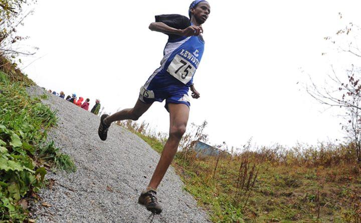 """Le 20 octobre 2012, Mohamed Awil, de Lewiston, décroche une seconde place dans le championnat de classe A de cross-country classe A pour garçons du Eastern Maine à Belfast, le 20 octobre 2012, photo d'archive. Awil est arrivé dans le Maine à l'âge de 13 ans après avoir passé son enfance dans un camp de réfugiés au Kenya. Awil, originaire de Somalie, dit maintenant que le Maine """"se sent comme à la maison""""."""