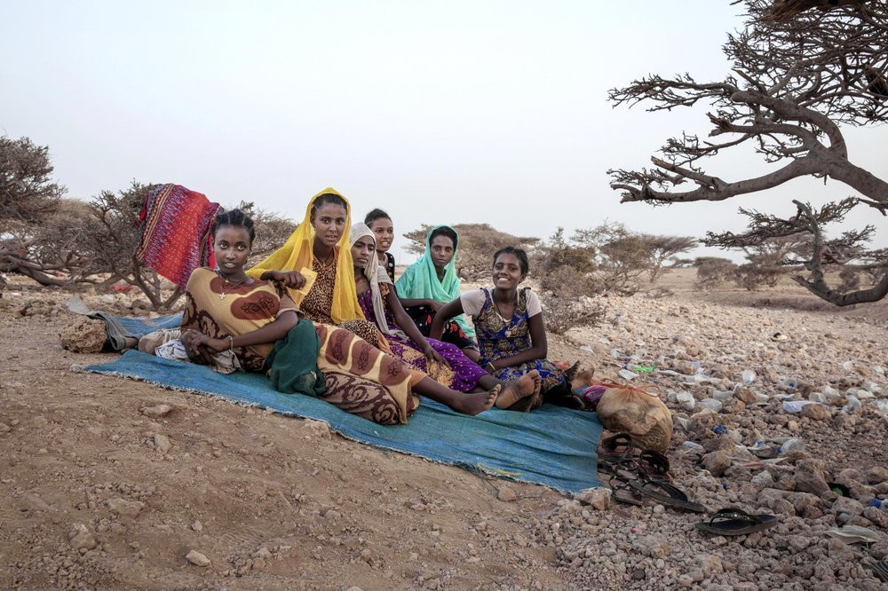 In this July 15, 2019 photo, Ethiopian Tigray teen migrants rest under a tree on the last stop of their journey before leaving by boat to Yemen in the evening, in Obock, Djibouti. An increasing number of the travelers include women and girls, who face rape and torture at the hands of human traffickers. (AP Photo/Nariman El-Mofty)