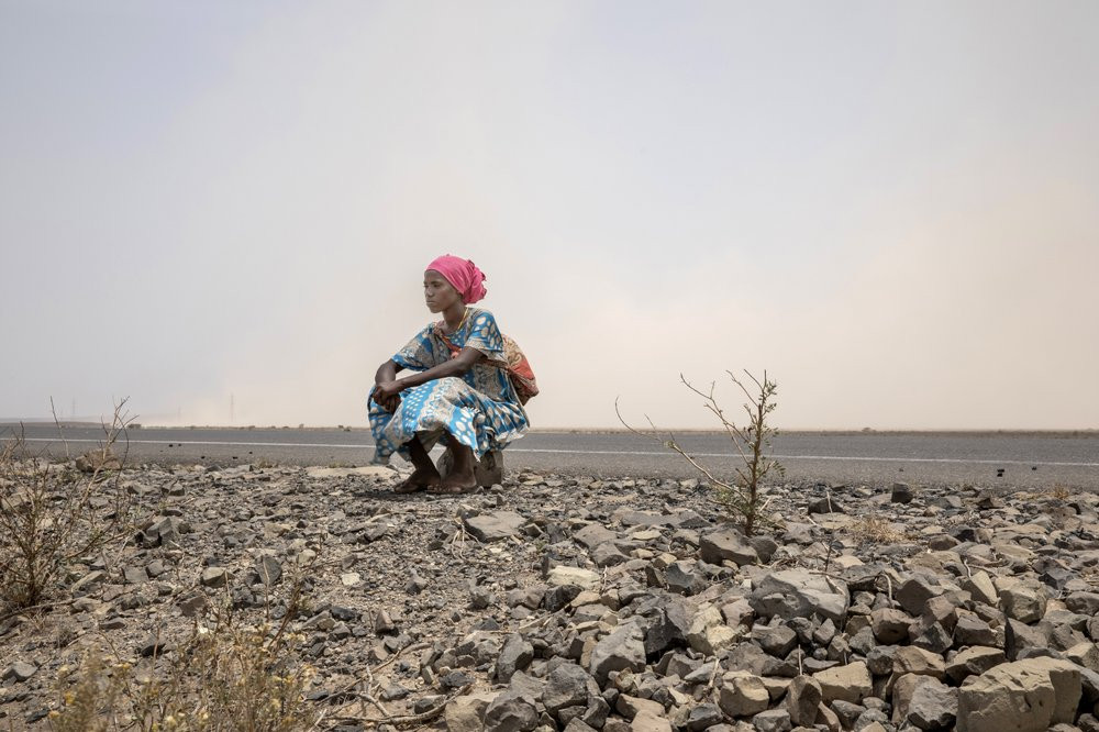 In this July 12, 2019 photo, 18-year-old Raheema Sanu, an Ethiopian migrant, rests on the side of a road, about 31 miles (50 kilometers) from Ali Sabeih, Djibouti. (AP Photo/Nariman El-Mofty)