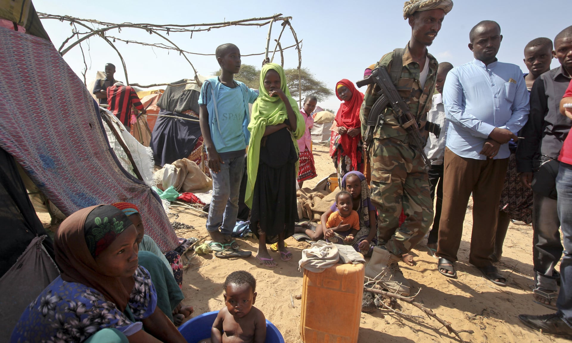 A soldier provides security as people forced from their homes gather at a camp in the Garasbaley area on the outskirts of Mogadishu, Somalia. Photograph: Farah Abdi Warsameh/AP