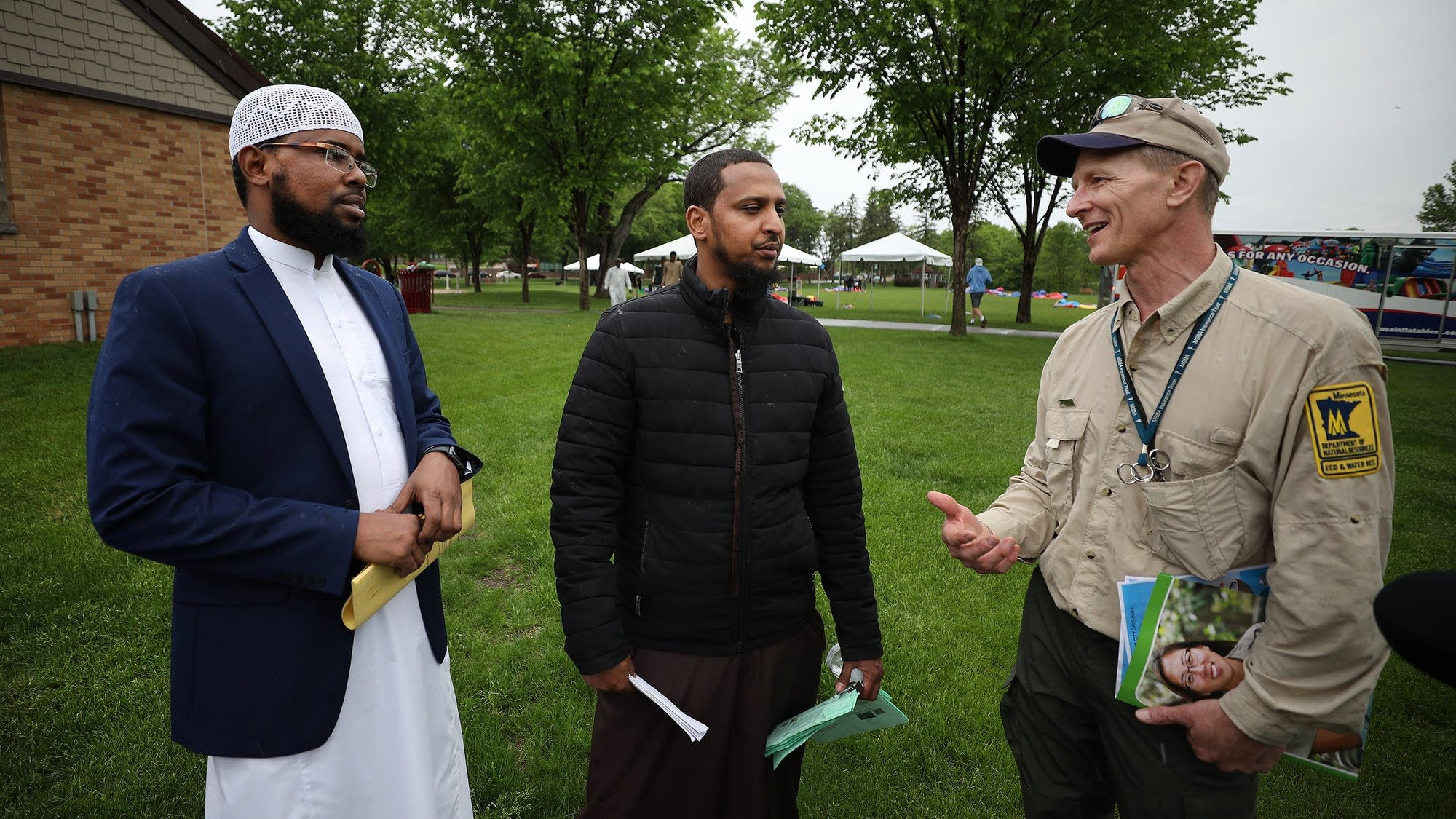 From left, Ahmed Hassan and Mohayadin Mohamed listen to Mark Hauck from the DNR talk about outdoor recreational activities. <br>Paul Middlestaedt for MPR News