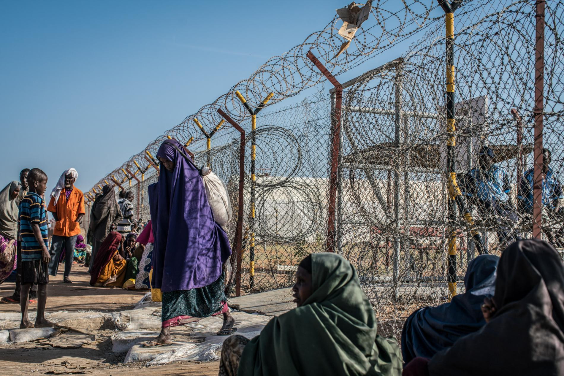 A woman leaves a food depot in Dadaab refugee camp, in northern Kenya, after receiving her rations. The population in Dadaab, estimated at nearly 220,000, has risen and fallen with droughts in the Horn of Africa. Along with droughts, famine, and desertification, decades of civil war have pushed tens of thousands of Somalis across Kenya's border into Dadaab.