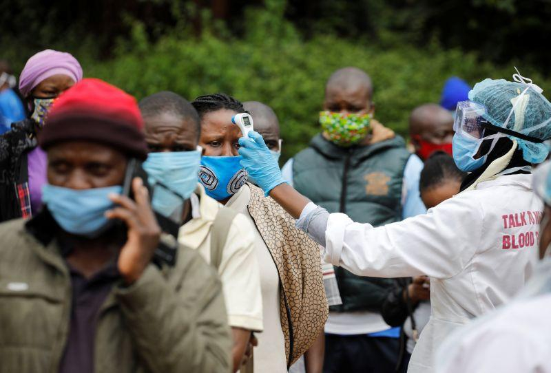 A health worker takes the temperature of a person standing in line for mass testing in an effort to stop the spread of the coronavirus disease (COVID-19) in the Kibera slum of Nairobi, Kenya, May 26, 2020. REUTERS/Baz Ratner