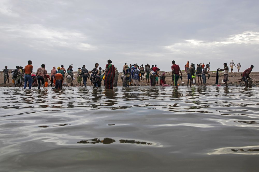 In this July 26, 2019 photo, Ethiopian migrants walk on the shores of Ras al-Ara, Lahj, Yemen, after disembarking from a boat. According to the U.N.'s International Organization for Migration the number of women making the trip jumped from nearly 15,000 in 2018 to more than 22,000 in 2019. The number of girls had an enormous increase, quadrupling from 2,075 to 8,360. Despite the many risks – smugglers' exploitation, hunger, drowning – they are undaunted. (AP Photo/Nariman El-Mofty)