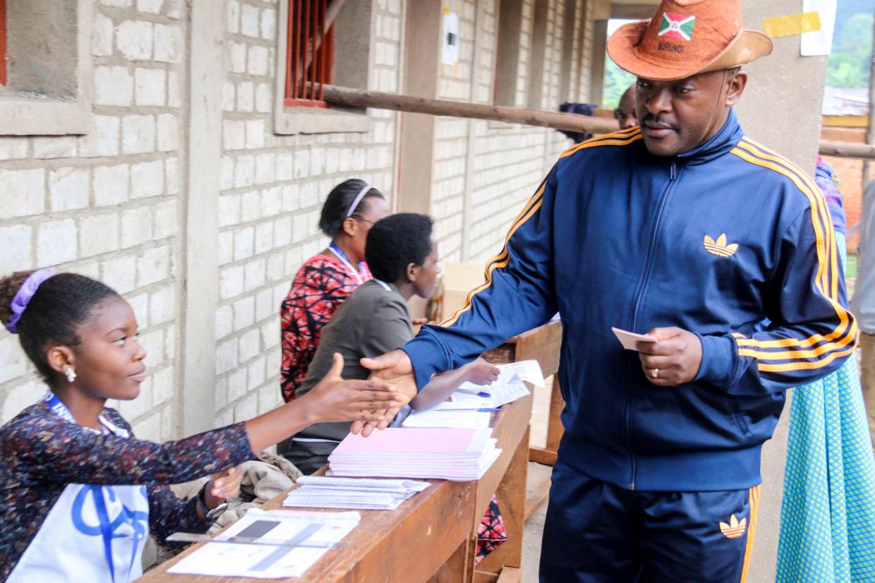 Burundi President Pierre Nkurunziza is registered by an electoral official before voting on a constitutional amendment referendum in Ngozi province, northern Burundi, May 17, 2018.