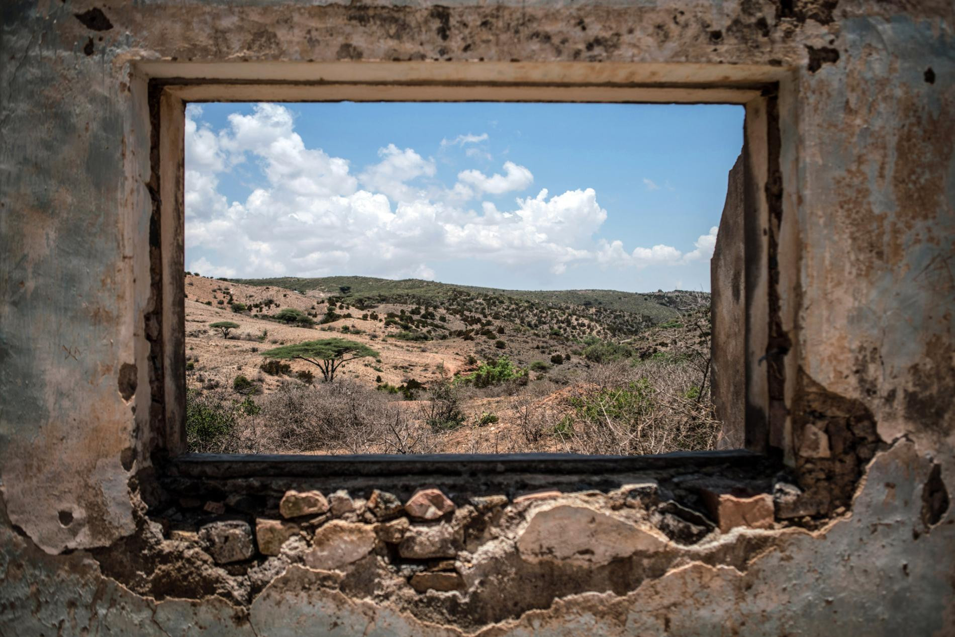 Somaliland's parched landscape is seen from inside a crumbling colonial building in Sheikh. Pressures from a changing climate, which is intensifying droughts, along with a decades-long civil war, are shattering the region's pastoral economy and forcing Somalis into IDP and refugee camps. Women in the camps live in constant fear of violence.