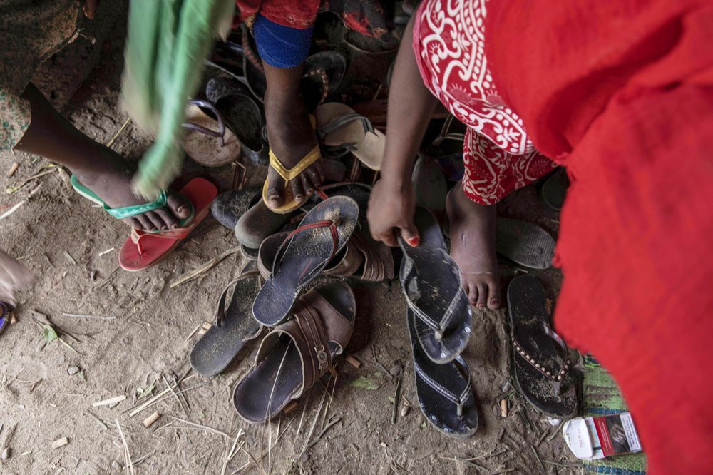 """In this July 26, 2019 photo, Ethiopian migrant girls put on their slippers to go and eat outside their lockup known in Arabic as a """"hosh,"""" in Ras al-Ara, Lahj, Yemen. Some lockups hold as many as 50 women at a time. The women will stay here for several days until their transportation is ready. (AP Photo/Nariman El-Mofty)"""