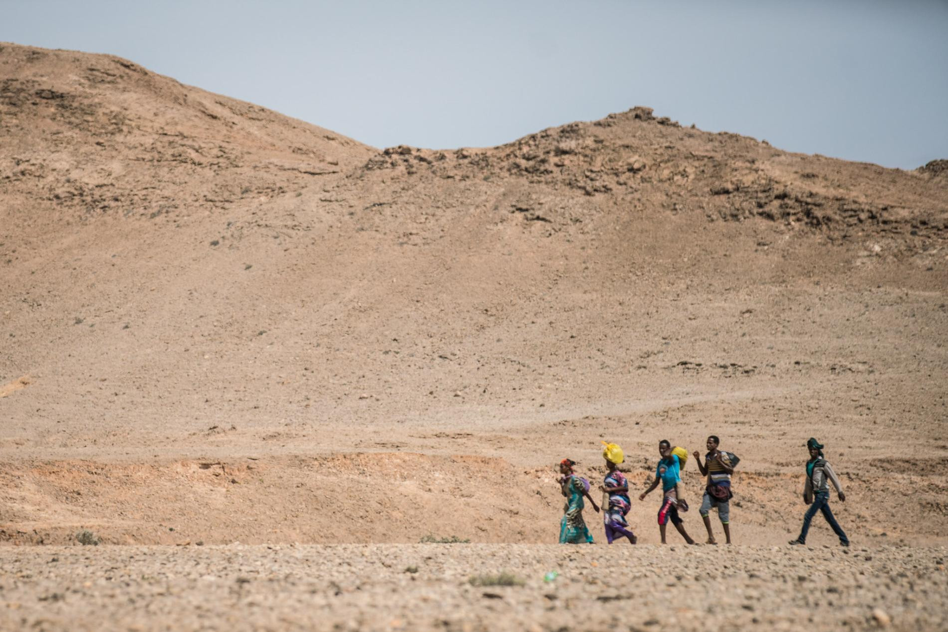 In 2016, Somali and Ethiopian migrants walk to caves outside Mareero, a smuggling hub in the autonomous region of Puntland, to await boats that will take them across the Gulf of Aden to Yemen and from there to Saudi Arabia and Gulf states—if they survive. For some stranded in IDP or refugee camps, this perilous journey is preferable to a life in limbo.