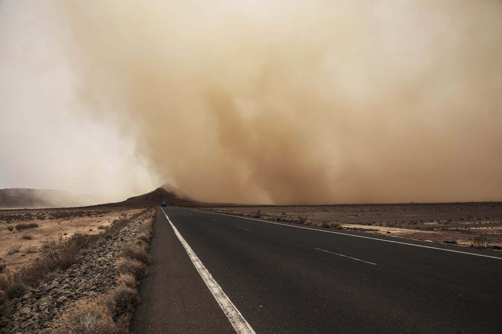 In this July 12, 2019 photo, a sandstorm gusts over a road where African migrants walk, around 50 kilometers (31 miles) from Djibouti. The number of girls among the migrants has had an enormous increase, quadrupling from 2,075 to 8,360 in one year. Despite the many risks of smugglers' exploitation, rape, hunger, drowning – they are undaunted. (AP Photo/Nariman El-Mofty)